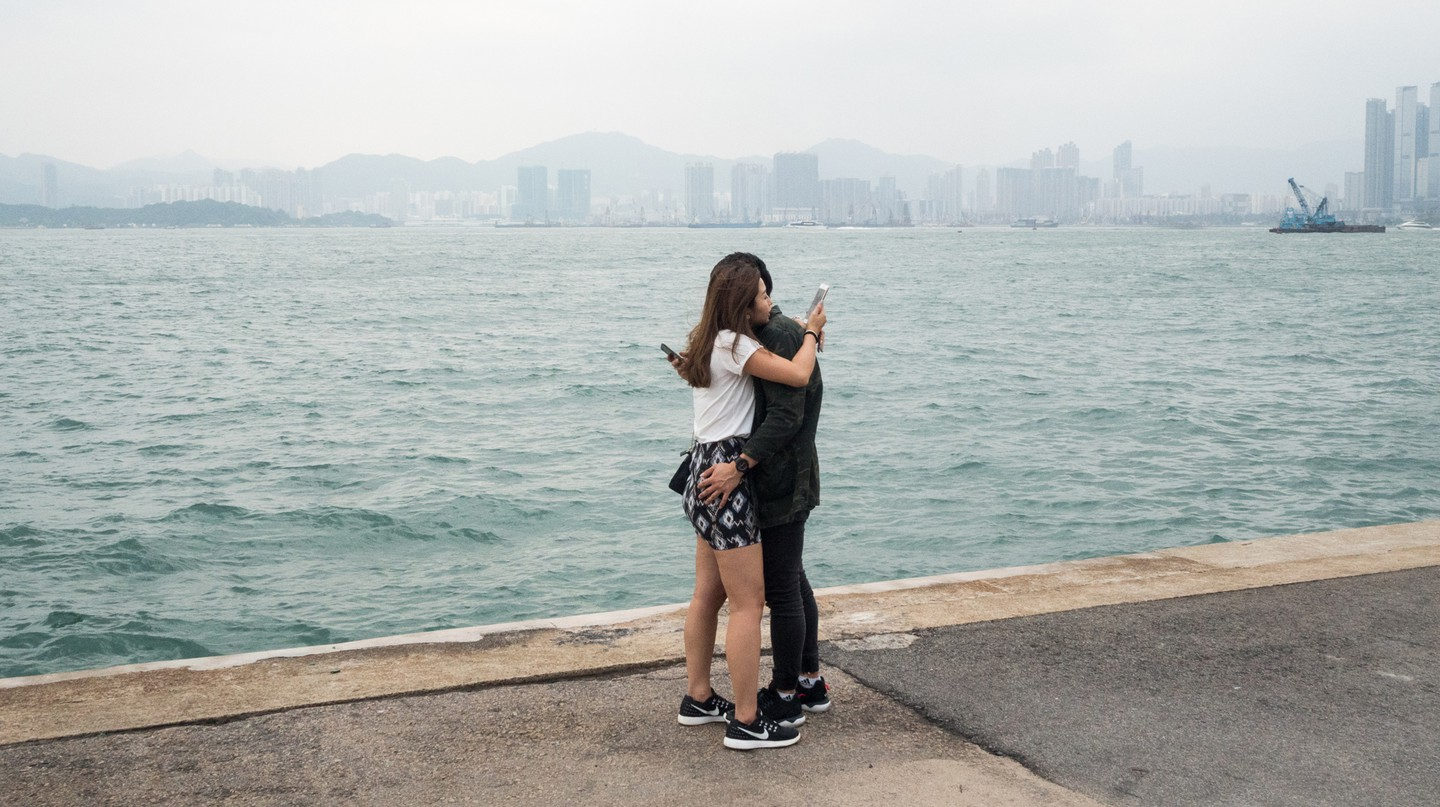 "A couple is sharing an embrace while checking their phones at the ""Instagram Pier"", Hong Kong"