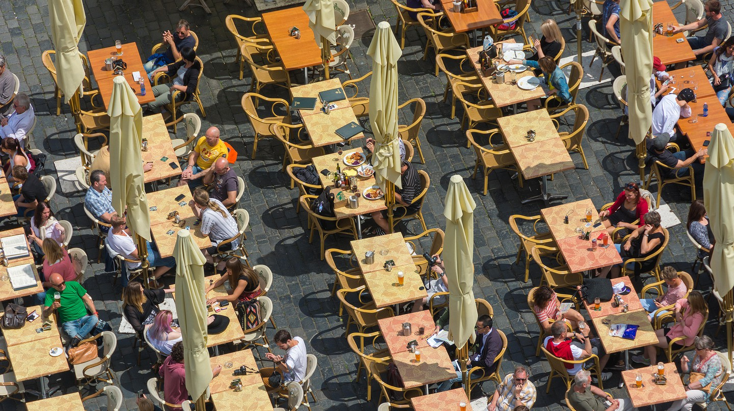 People dine at an outdoor restaurant in Prague, Czech Republic