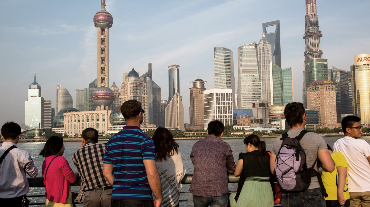 A tour group stand on the waterfront overlooking the Huangpu River and skyscrapers in the Pudong business district of Shanghai, China