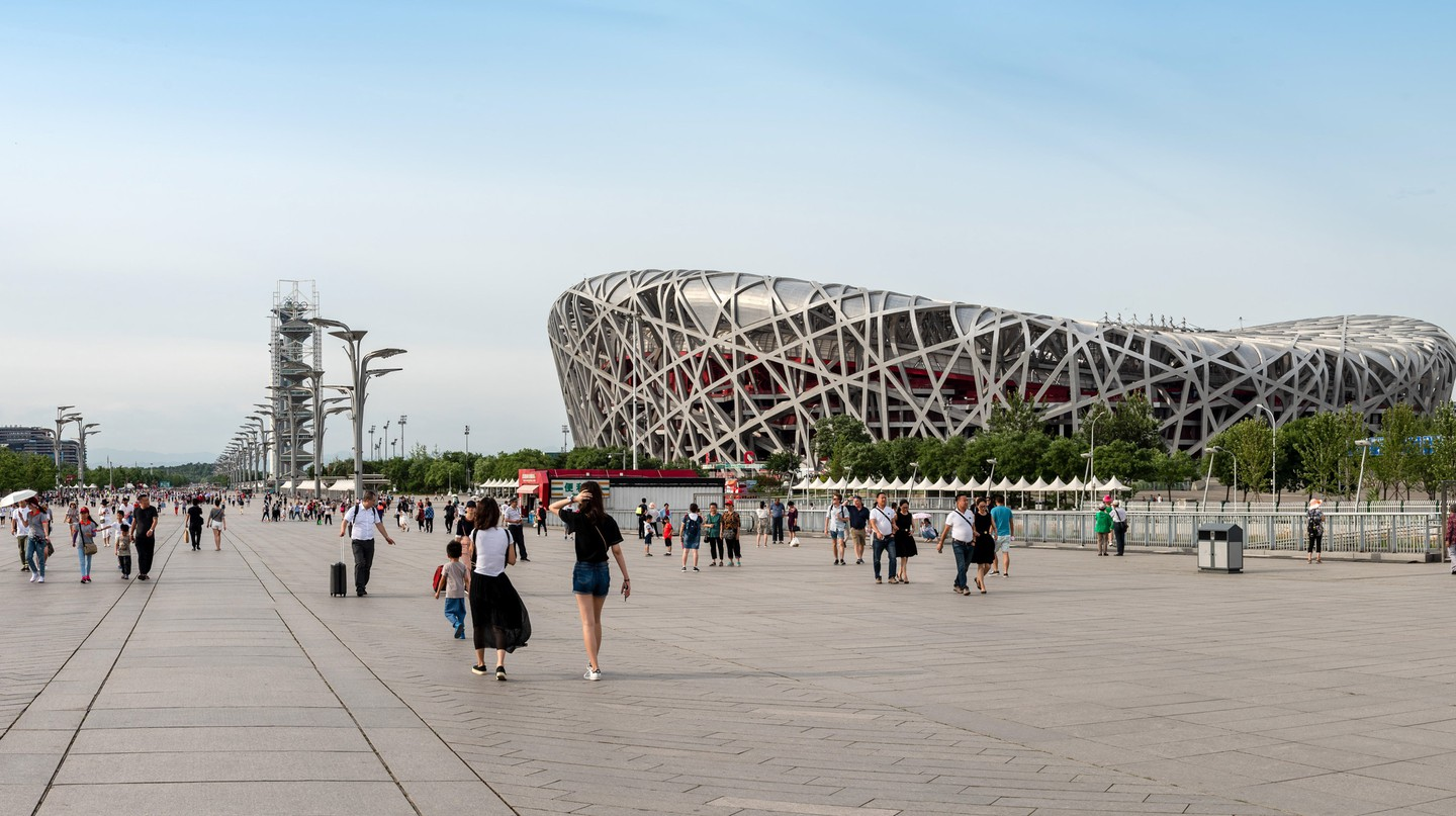 People walk around the Olympic Park near the Bird's Nest Stadium in Beijing, China