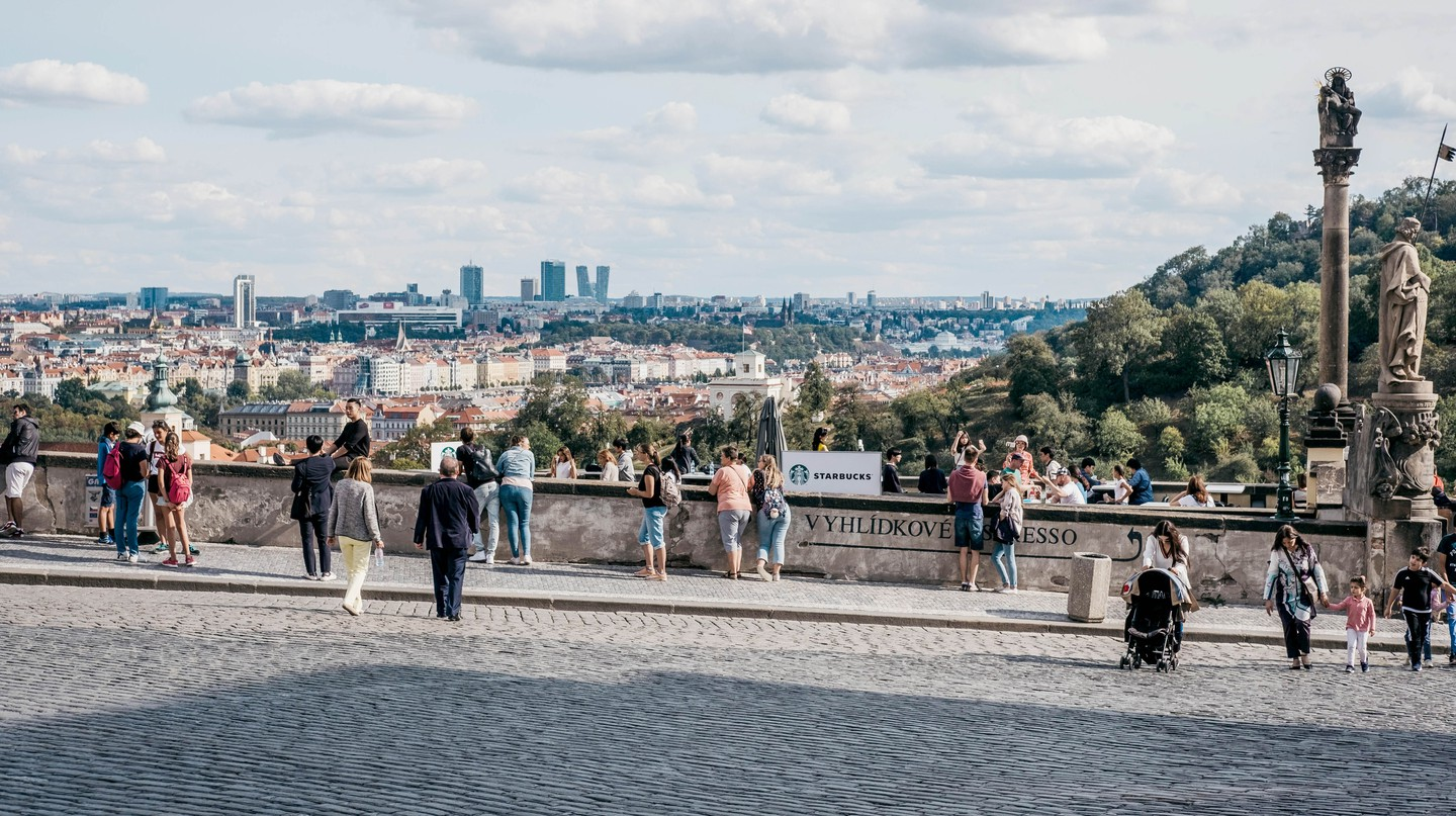 People walk on a viewing platform near Prague Castle