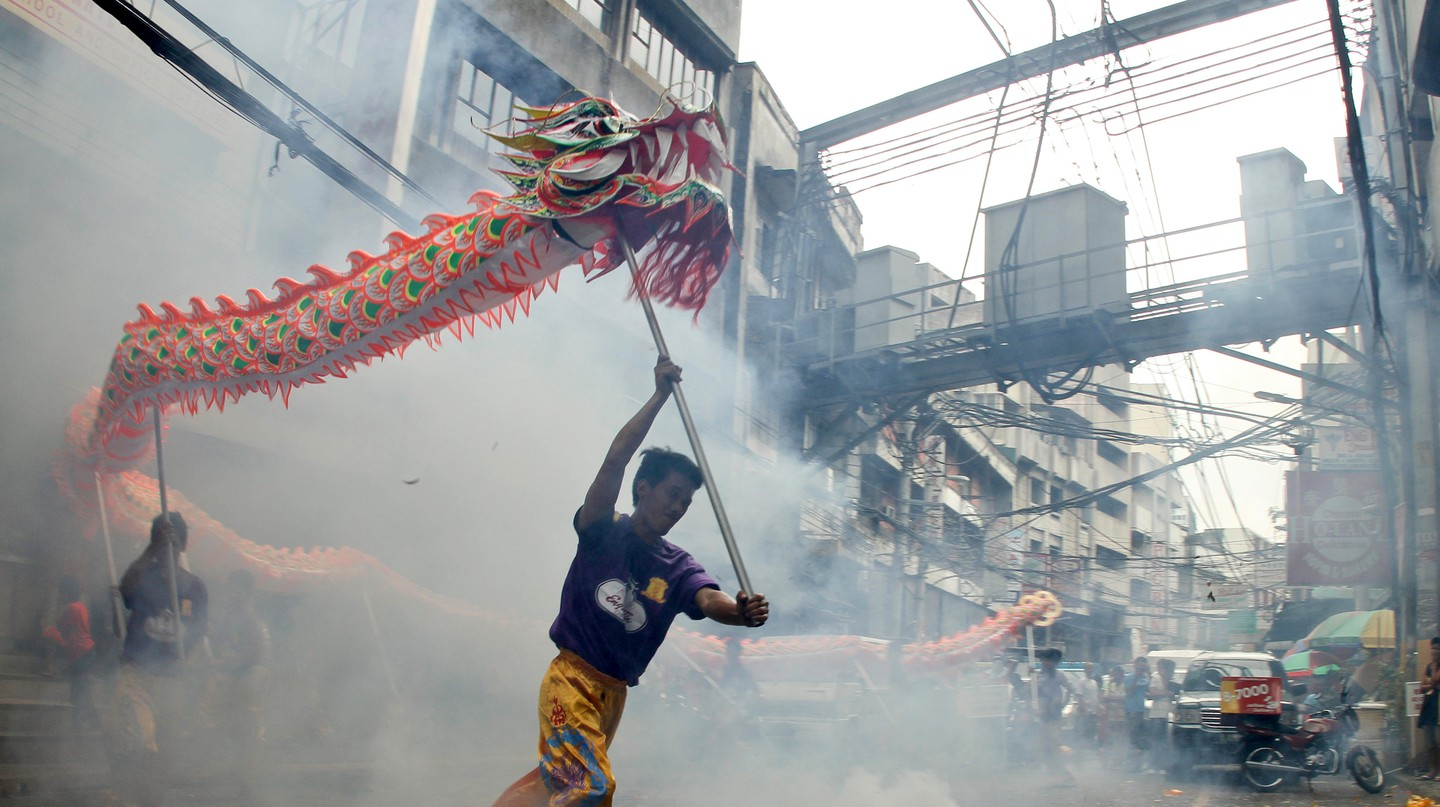 Street performers carry their dragon around firecrackers in Chinatown, Manila