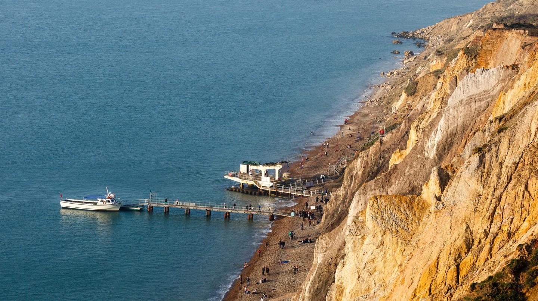 People take a stroll along Alum Bay, Isle of Wight, England