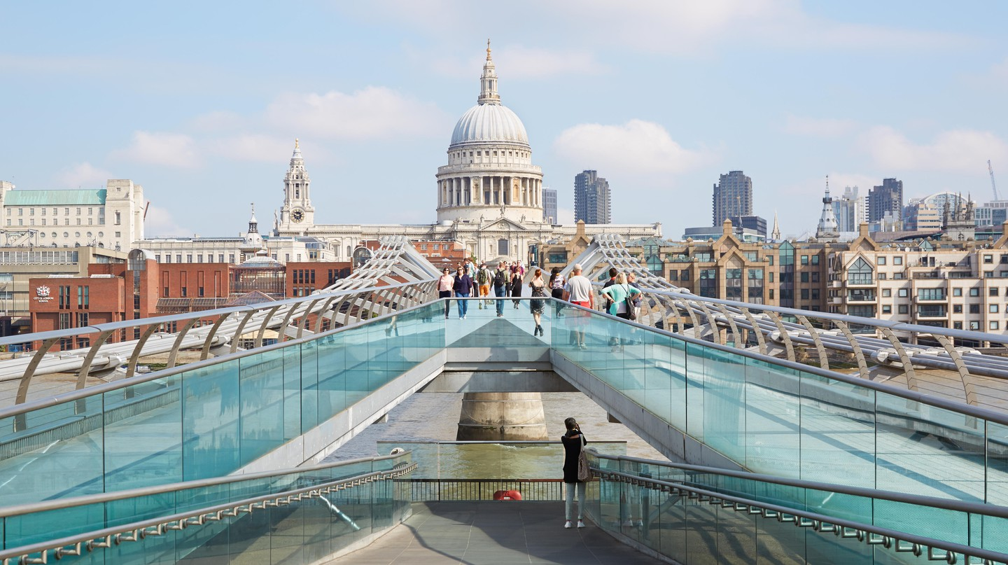 People walk across the Millennium Bridge in London, with St Paul's Cathedral in the background