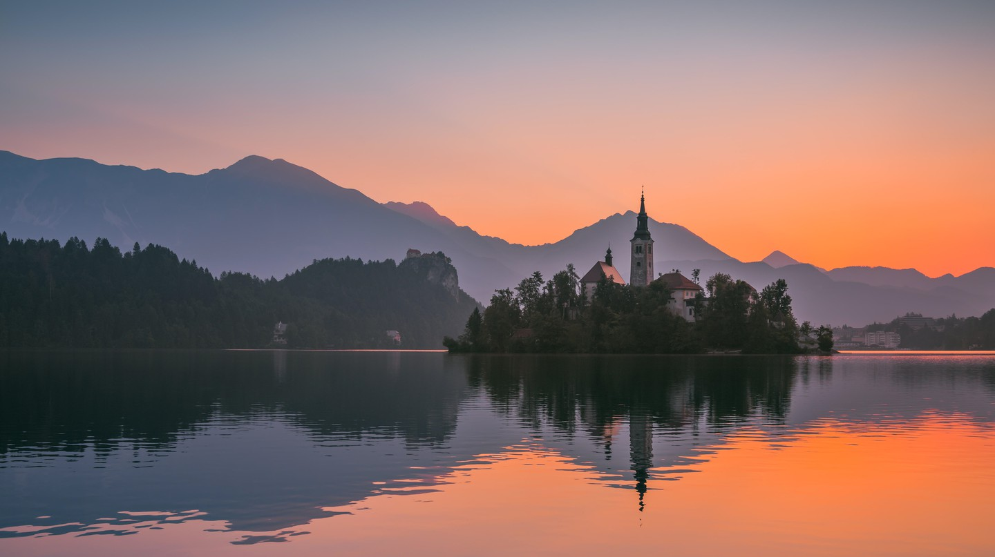 Little Island with Catholic Church in Bled Lake, Slovenia at sunrise.