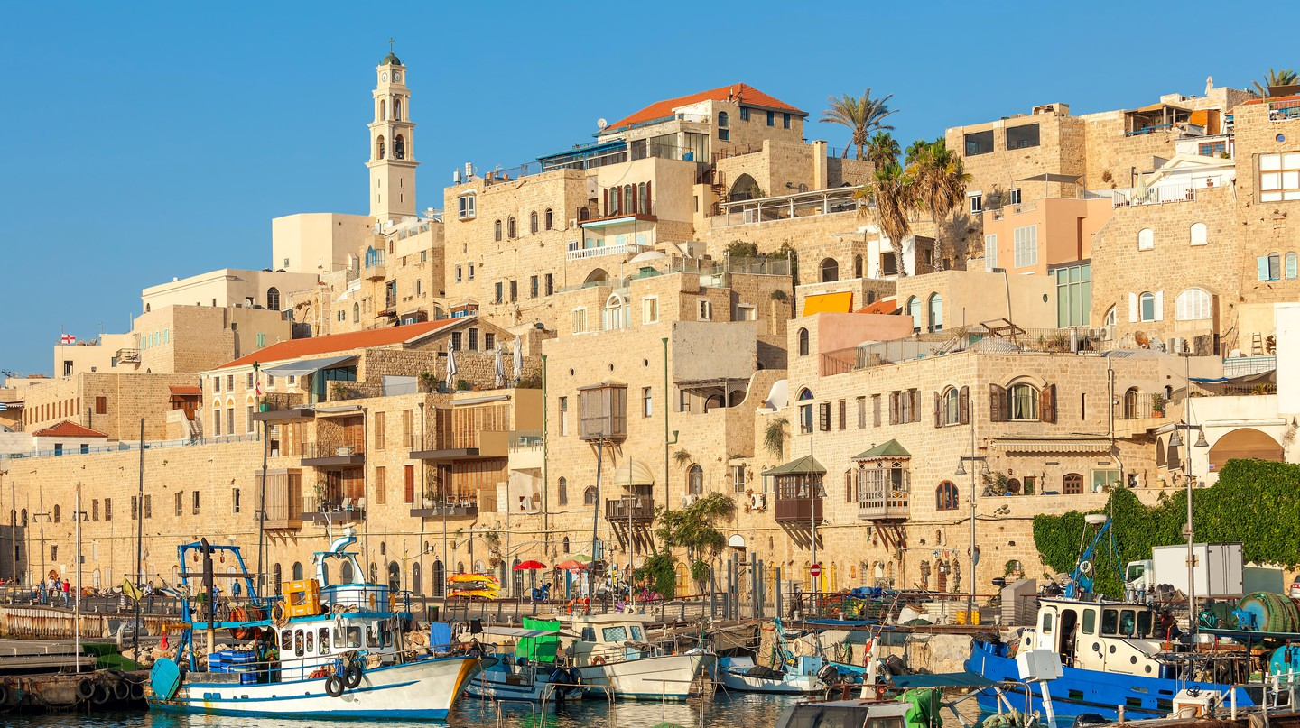 Boats crowd a harbour in Jaffa under an empty sky