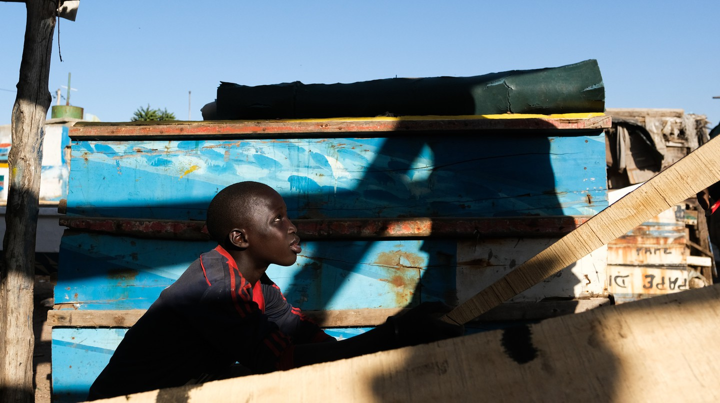 12-year-old Alioune helps his father, master carpenter Mbaye Gningue, build a pirogue in Dakar