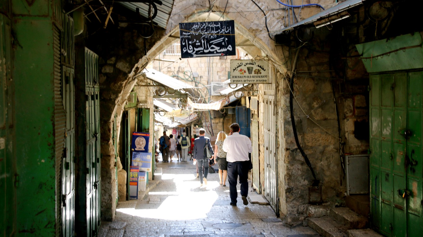 People stroll along an alley of the bazaar in the Old City of Jerusalem, Israel