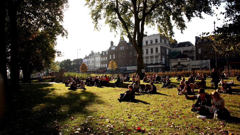 A Sunday crowd enjoys the late afternoon sun on Islington Green