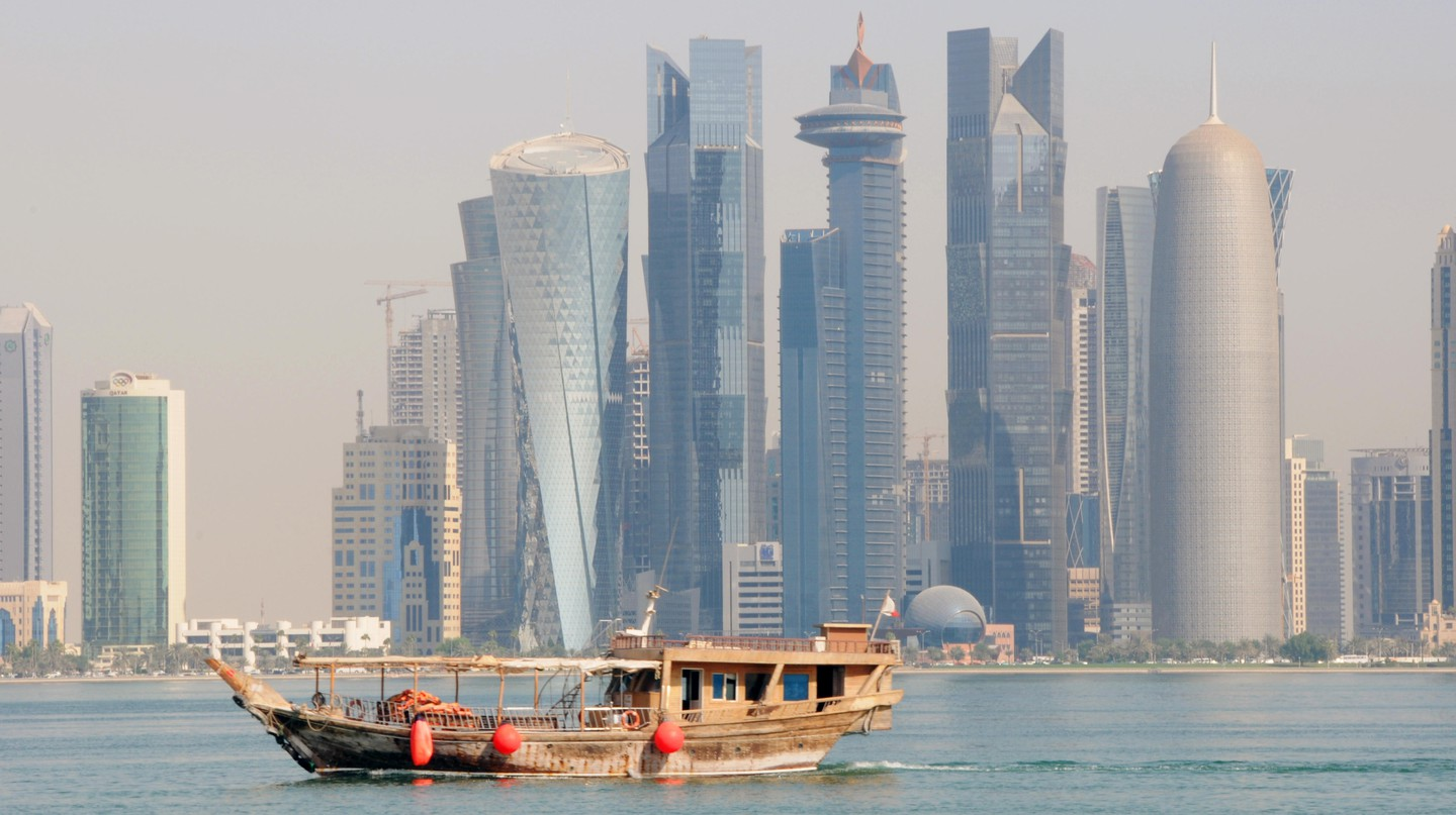 A traditional dhow cruises past the Doha skyline
