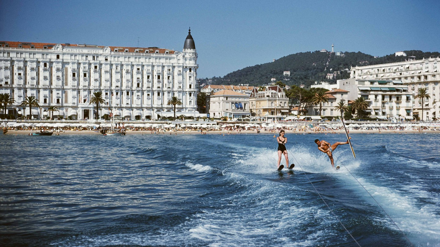 Holidaymakers waterski in front of the Carlton Hotel, Cannes, 1958