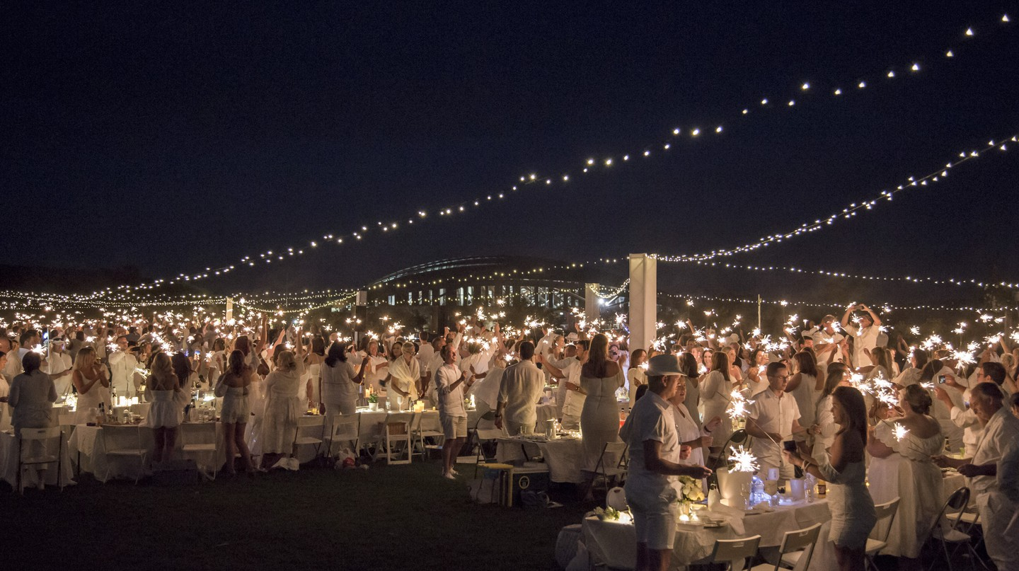 Participants in 2018's Diner en Blanc light up the night with sparklers