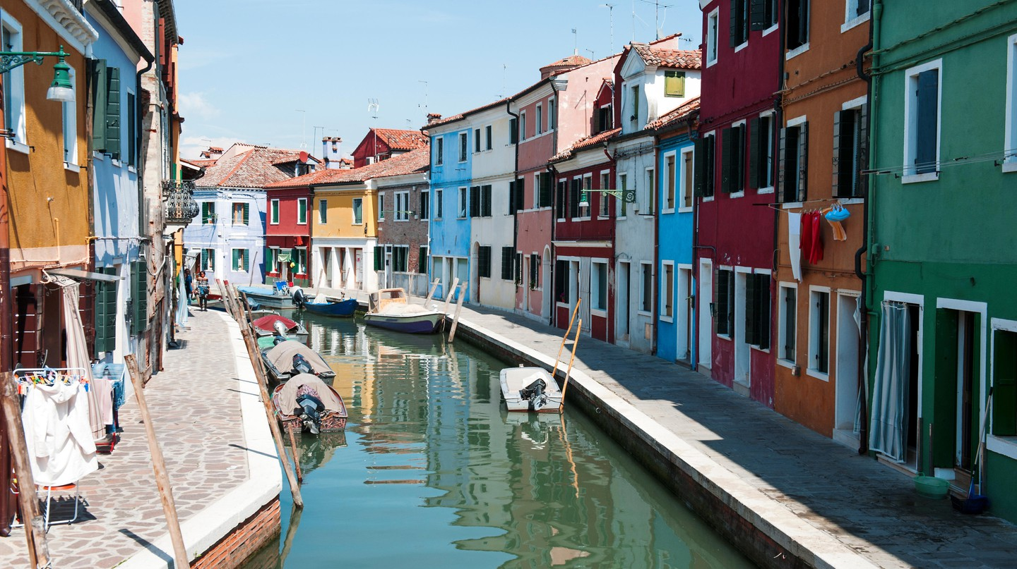 Save money on accommodation so you can take an excursion to the brightly colourful houses in Burano