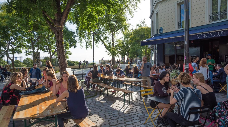 People enjoy drinks in the sun outside French restaurant Moncoeur Belleville in Paris