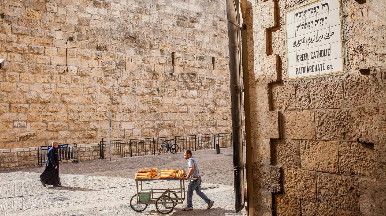 A bread vendor walks down Greek Catholic Patriarchate Street, near Jaffa Gate in the Old City, Jerusalem