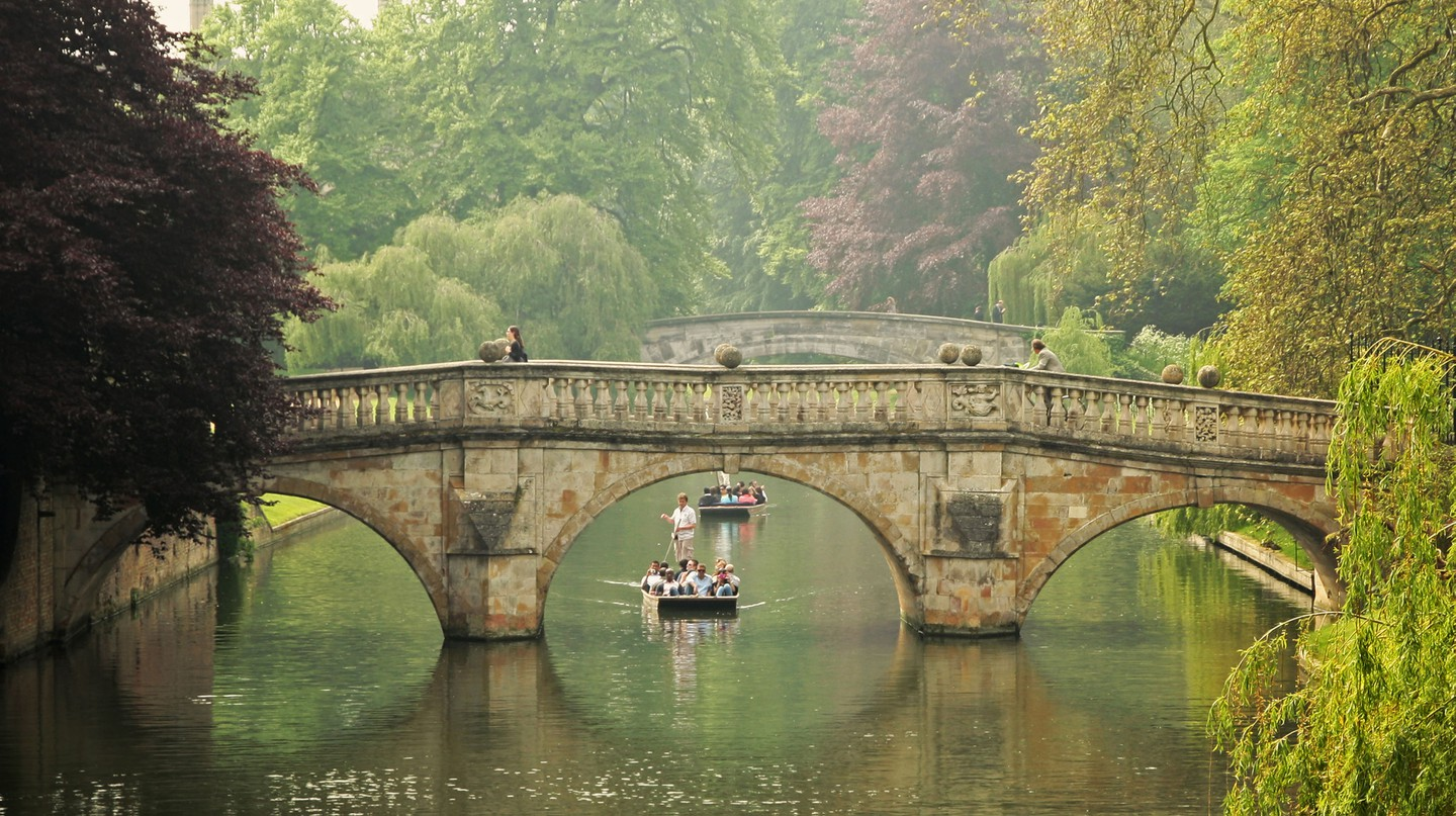 A punt passes under Clare College Bridge on the River Cam, Cambridge