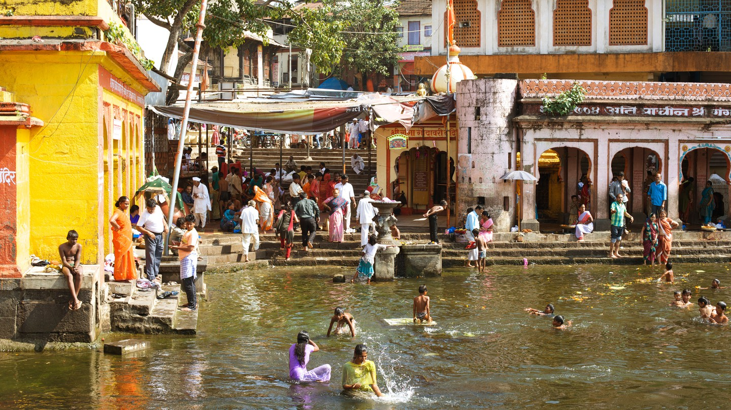 People bathe in the holy water of the Godavari River at Ram Kund