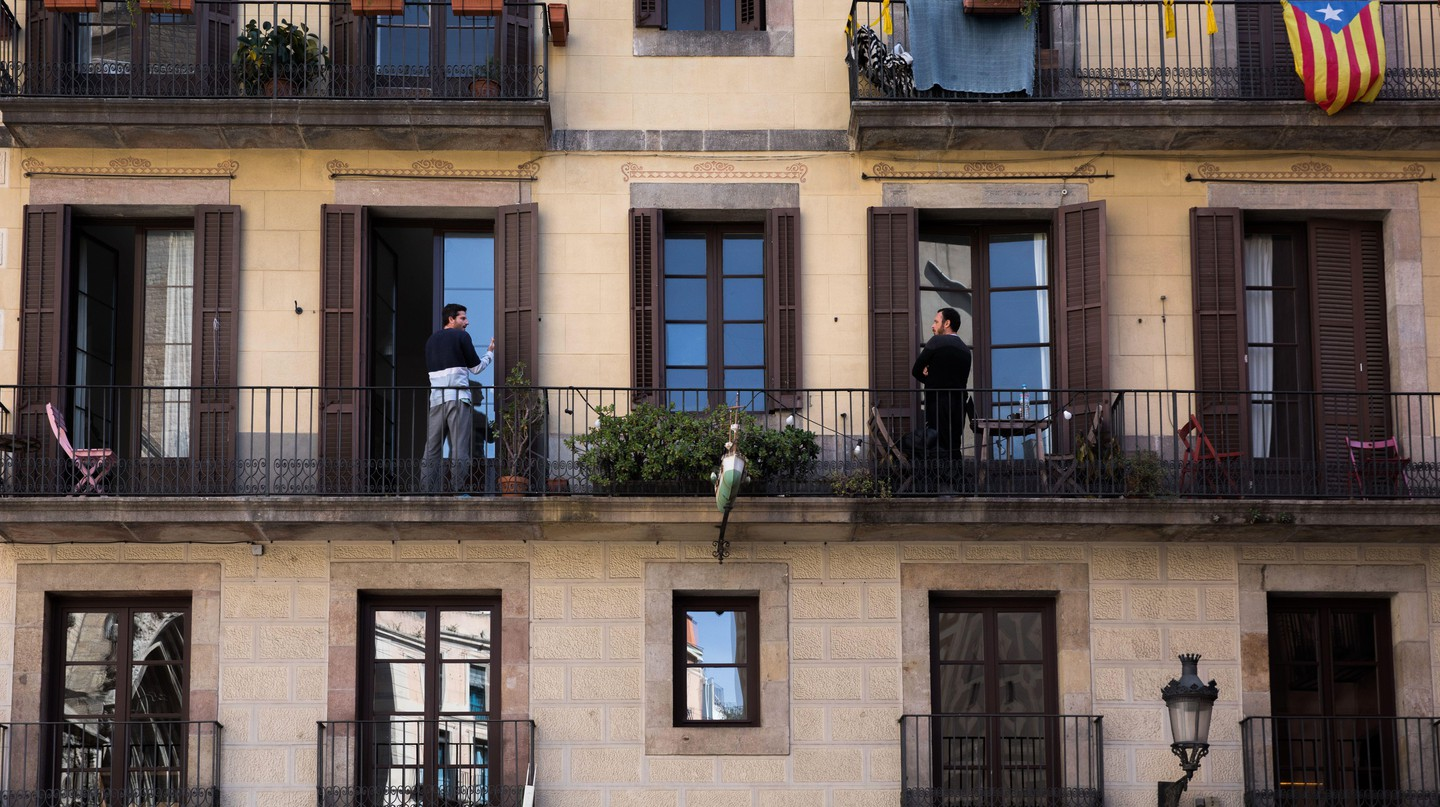 Two neighbours talk from their own balconies during Barcelona's lockdown