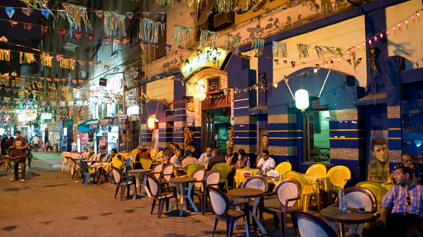 A street lined with cafes and restaurants with people sitting at tables outside enjoying the best of Downtown Cairo
