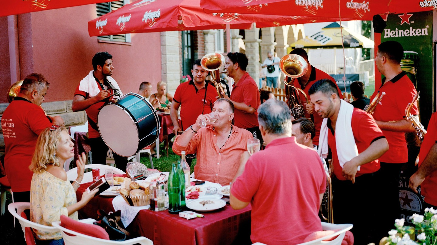 Guests are serenaded by bands while eating at the 2019 Guča Trumpet Festival