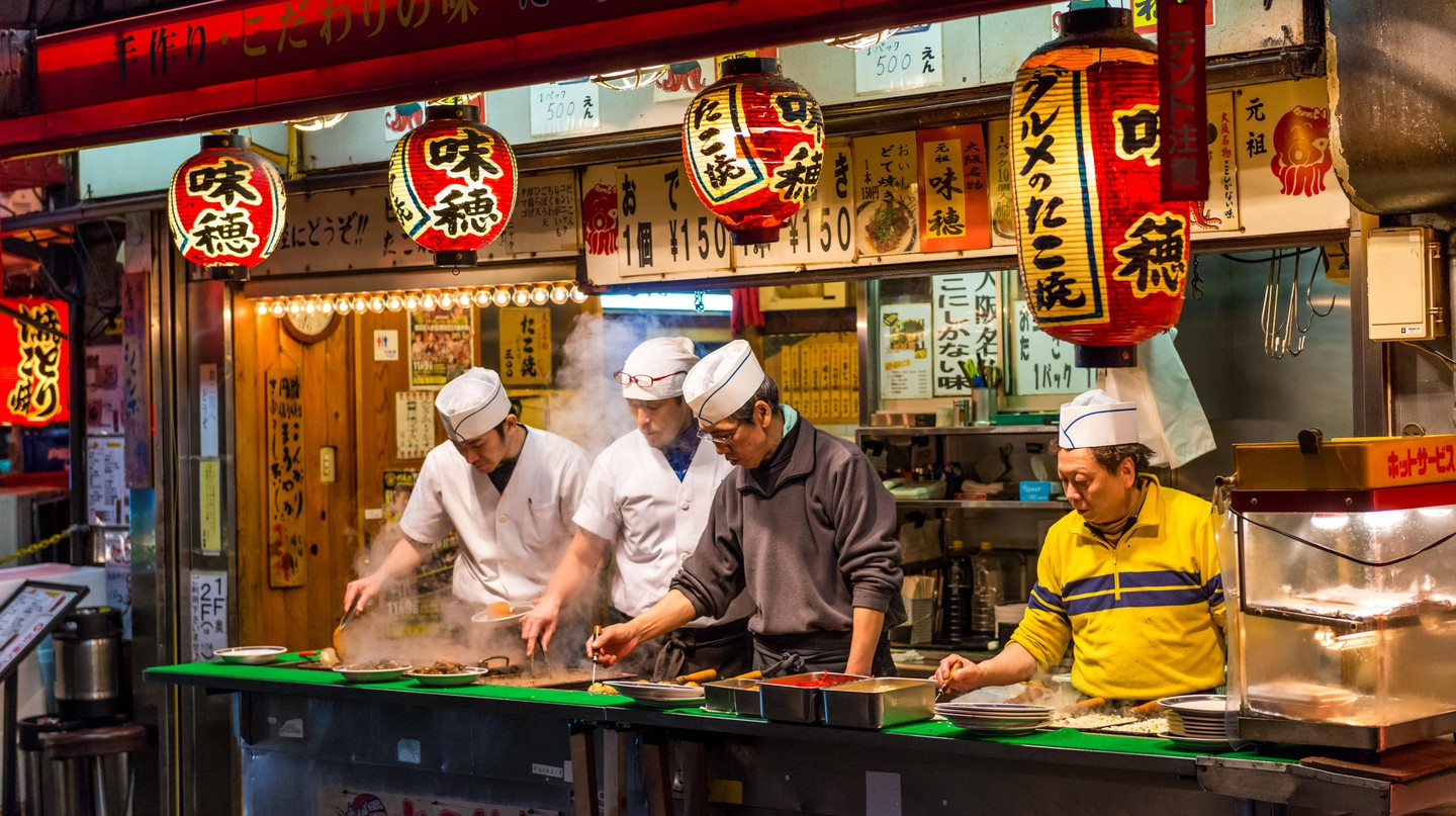 Japanese chefs prepare 'takoyaki' and other snack foods at a stall in Osaka, Japan.
