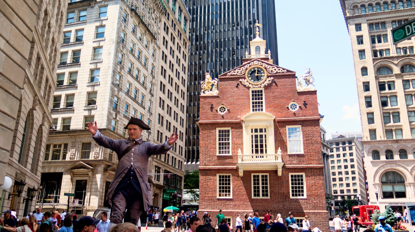 A guide in traditional costume stands in front of the Old Statehouse on the Freedom Trail in Boston