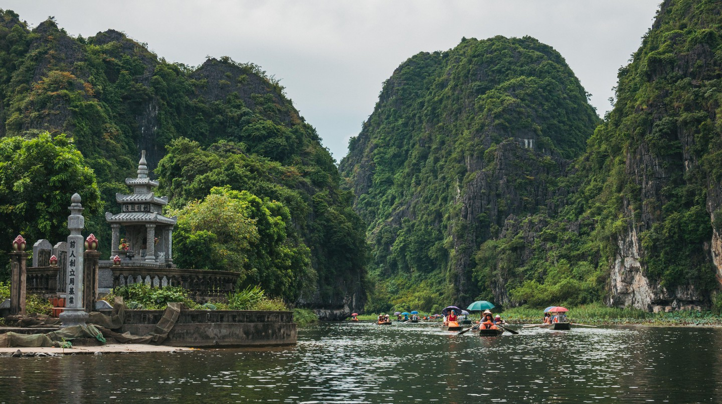 Tourists in boats row up the Ngo Dong River through limestone mountains and caves in Tam Coc, Ninh Binh Province