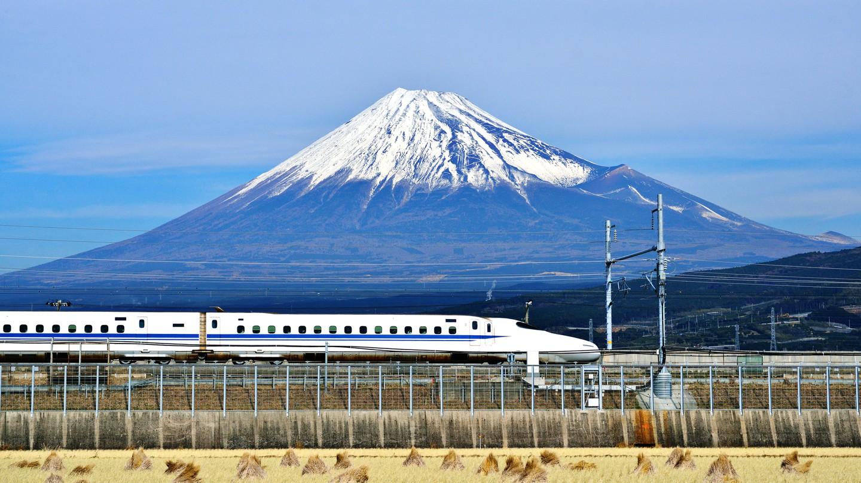 A high-speed bullet train passes below Mount Fuji in Japan