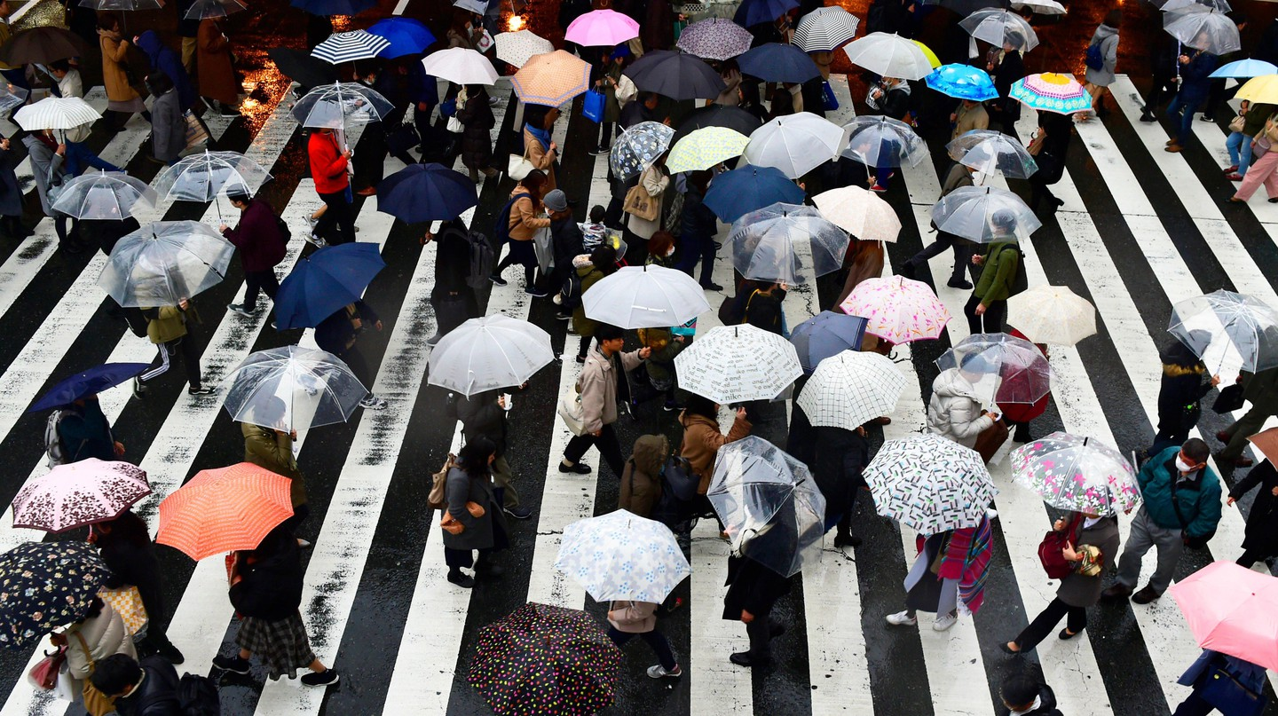 Pedestrians with multi colored umbrellas in Umeda district, Osaka, Japan.