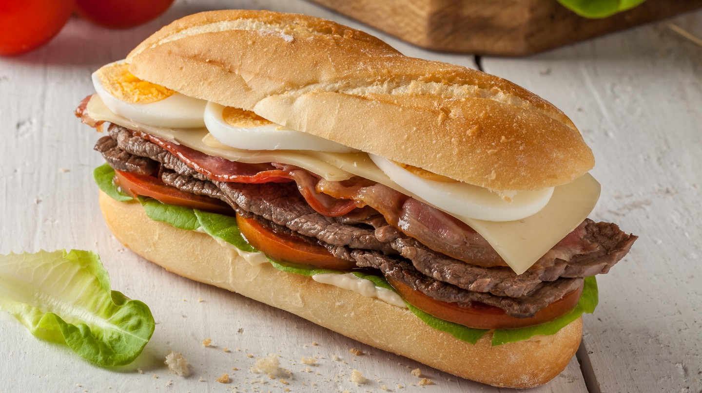 Chivito is a typical sandwich from Uruguay, often featuring lettuce, tomato, bacon, beef, fried or boiled eggs and cheese