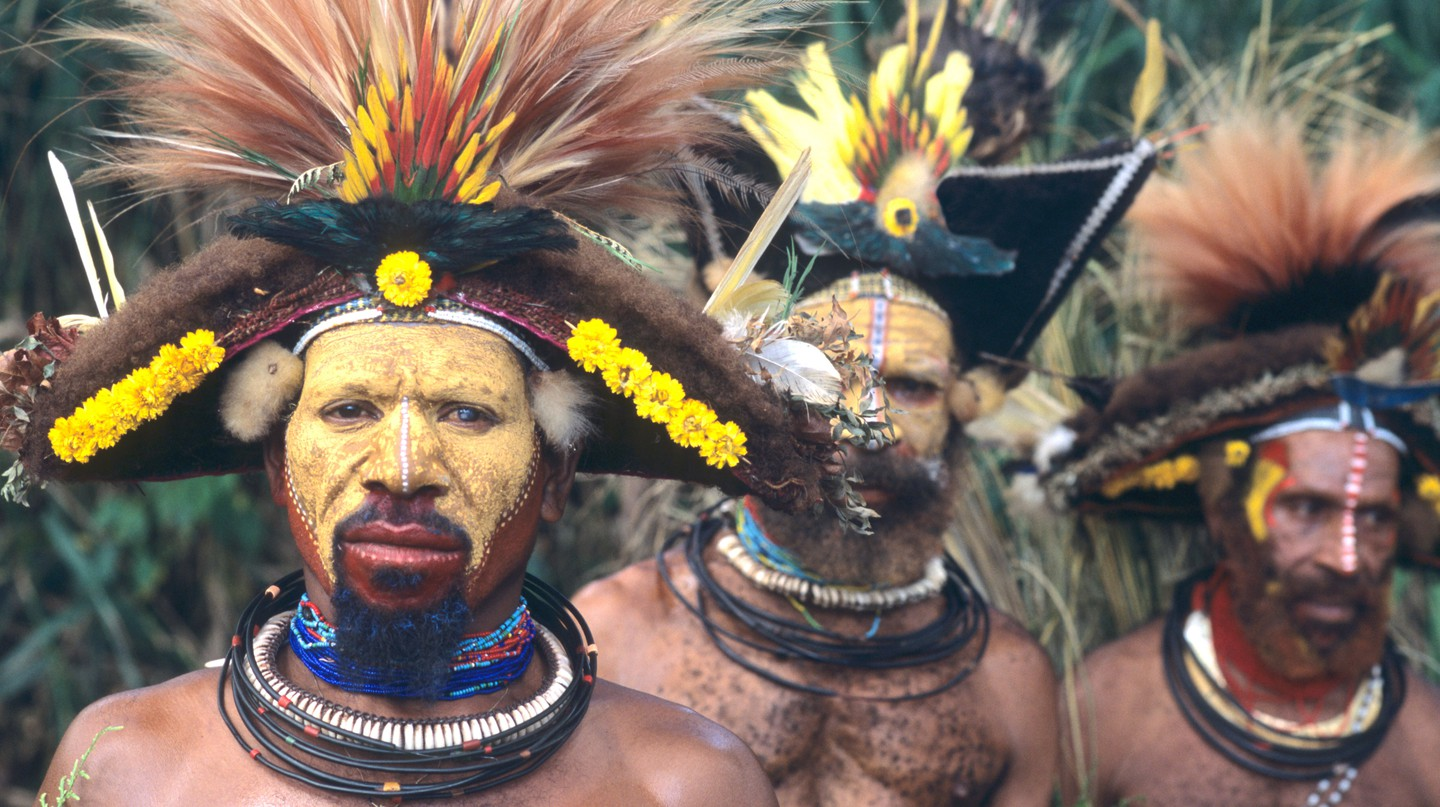 Huli Wigmen wear wigs decorated with feathers and ochre and cover their faces in yellow clay