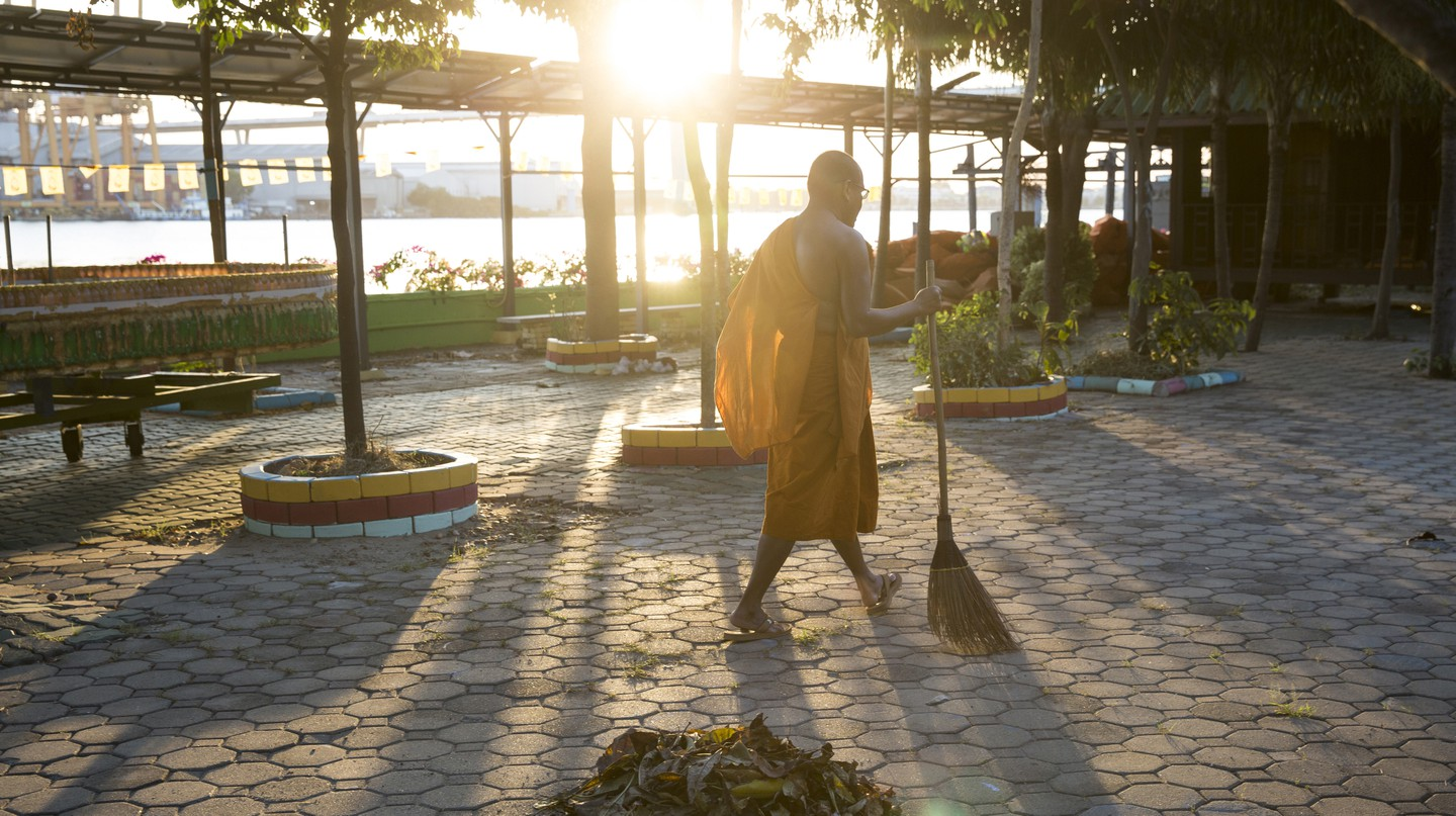 Phra Mahapranom Dhammalangkaro, abbot of Chak Deang Temple, sweeps the temple for leaves at the end of the day