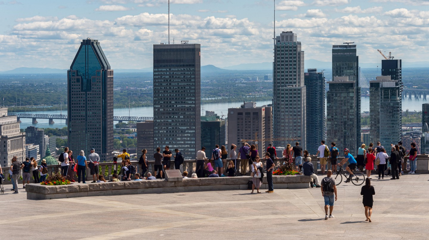 Tourists enjoying view of Montreal skyline from Kondiaronk Belvedere at Chalet du Mont-Royal