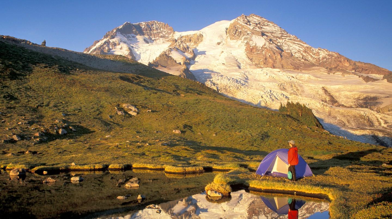 Woman setting up tent by lake below Mount Rainier Mount Rainier National Park, Washington.