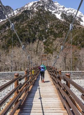 Woman walking over Myojin Bridge, Japanese Alps, Kamikochi, Matsumoto, Nagano, Japan