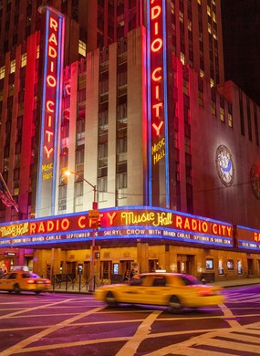 Taxis drive by Radio City Music Hall in Manhattan, New York City, USA