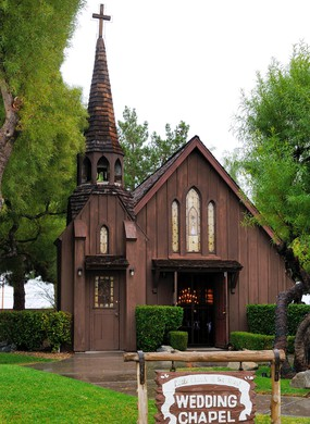 View of the main facade of a small wood wedding chapel near the famous Las Vegas enter sign in the Strip, in Las Vegas, Nevada.