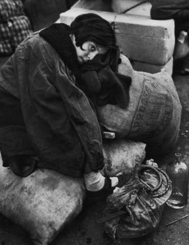 Little girl resting during the evacuation of the city, Barcelona, 1939 © Robert Capa/Magnum Photos