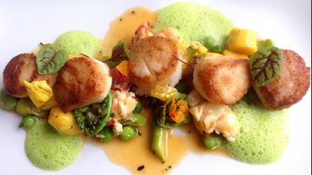 Seared day boat scallops with saffron gnocchi, poached lobster, and early spring vegetable