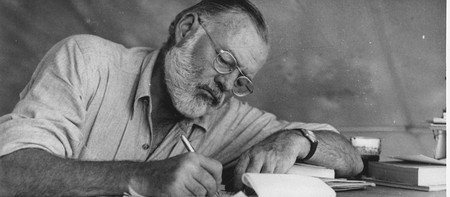 Ernest Hemingway writing at Campsite in Kenya | © Look Magazine/WikiCommons