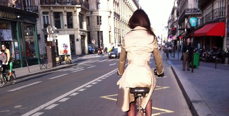 Stylish woman riding a bicycle down a Paris street │© ParisSharing