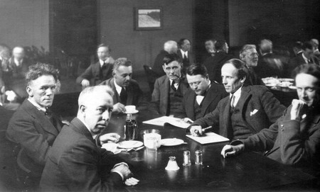 Six of the Group of Seven, plus their friend Barker Fairley, in 1920. From left to right: Frederick Varley, A. Y. Jackson, Lawren Harris, Fairley, Frank Johnston, Arthur Lismer, and J. E. H. MacDonald. At The Arts and Letters Club of Toronto | Public Domain/WikiCommons