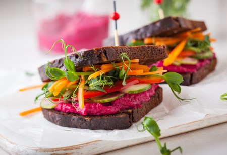 Gluten-free vegan sandwiches with beet hummus, raw vegetables and sprouts