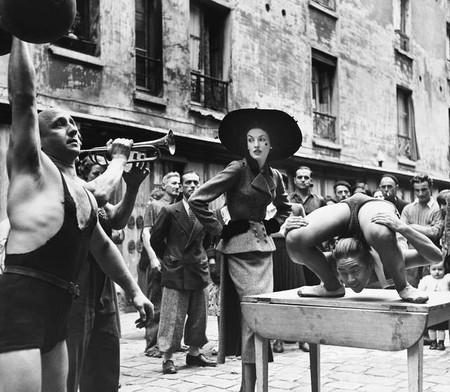 Elise Daniels with street performers, suit by Balenciaga, Le Marais, Paris, August 1948. Photograph by Richard Avedon. © The Richard Avedon Foundation