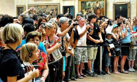 Crowd photographing the Mona Lisa │© tomarthur / Wikimedia Commons