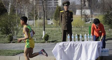 A soldier stands guard as runners pass during the 2017 Pyongyang Marathon | © AP/REX/Shutterstock
