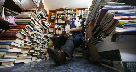 Jose Alberto Gutierrez sits among piles of books at his home in Bogota, Colombia | © Fernando Vergara/AP/REX/Shutterstock