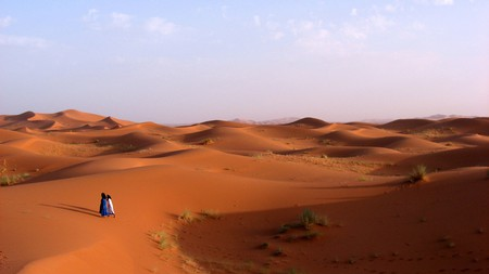 Two people walking across the desert