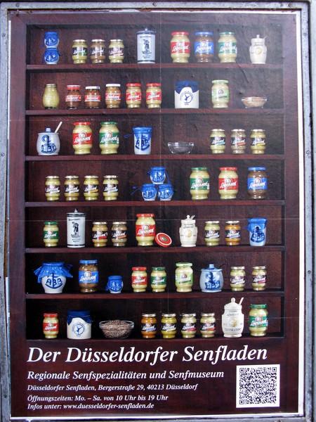"<a href=""https://commons.wikimedia.org/wiki/File:D%C3%BCsseldorfer_Senfladen,_Plakat.jpg"" target=""_blank"" rel=""noopener noreferrer"">Düsseldorfer Senfladen potcard | © Andreas Schwarzkopf / Wikimedia Commons</a>"