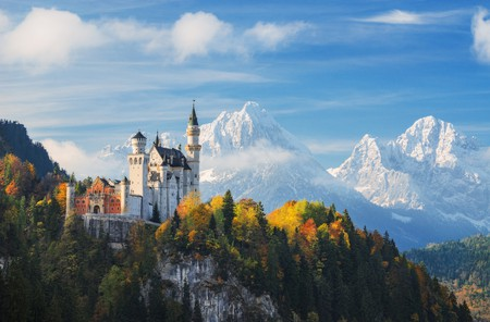 Germany. The famous Neuschwanstein Castle in the background of snowy mountains and trees with yellow and green leaves. | © Naumenko Aleksandr / Shutterstock